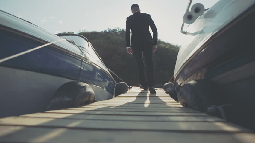 Stylish businessman is confident near a marine with luxury yachts against a deep blue sky and sea with the sun filtering through his neck. #12275414