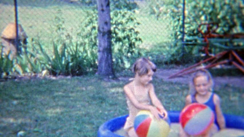 FLINT, MICHIGAN 1965: Young girls splashing in small backyard pool.