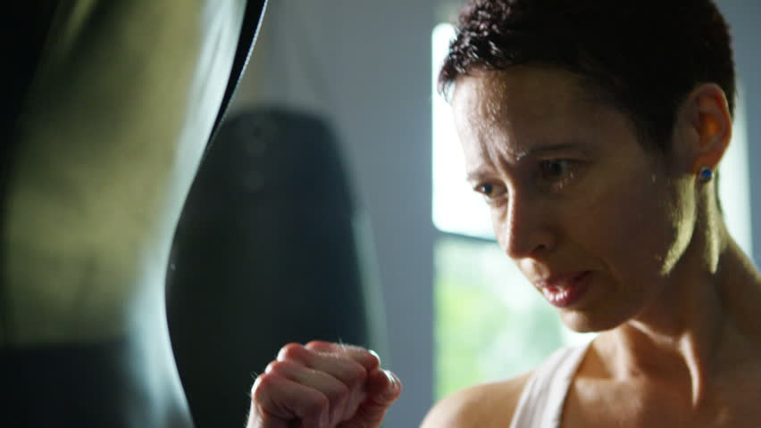 4K Female martial artist or boxer training with a punch bag at the gym. Shot on RED Epic. #12287453