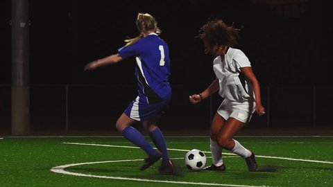 A female soccer player dribbles down the field during a game at night