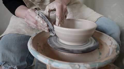 Woman artist gives shape to plate on potter's wheel