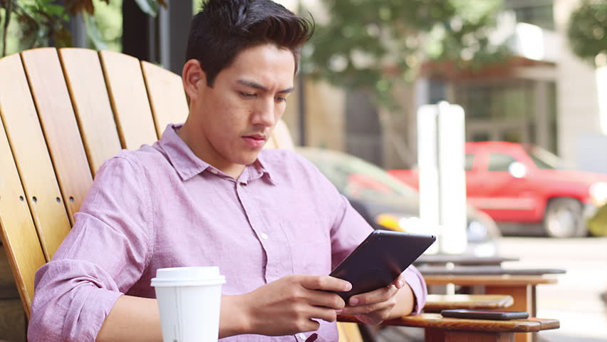A young man sitting outside using his tablet and drinking coffee | Shutterstock HD Video #12306158
