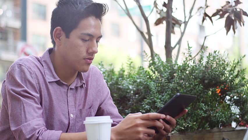 A young man sitting outside using his tablet and drinking coffee, looking around for someone | Shutterstock HD Video #12306293