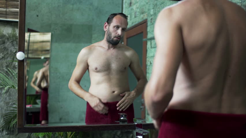 Young man in towel checking his stomach in bathroom