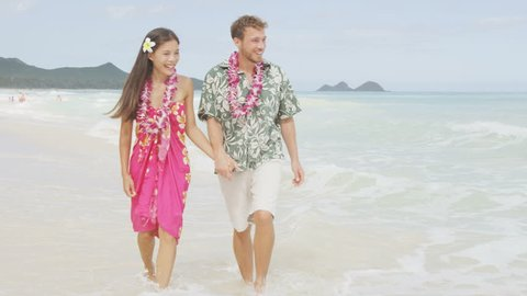 Happy couple having fun running on Hawaii beach vacations in Hawaiian clothing wearing Aloha shirt and pink sarong sun dress and flower leis for traditional wedding or honeymoon concept. RED EPIC.