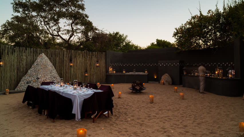 A linear dolly day-to-night (holy grail) timelapse of a luxurious boma (outside dining area) getting prepared for dinner around the fire under the African night sky at a private 5 star lodge. 4K