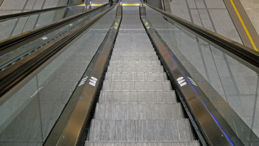 The look of the escalator while going down. There is a yellow line and a handle on the side for people to hold while riding | Shutterstock HD Video #12372866