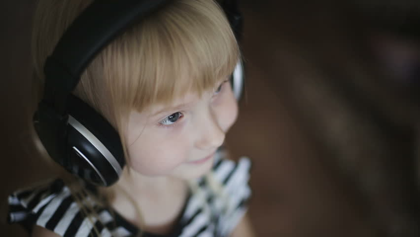 Close up face a little girl in headphones