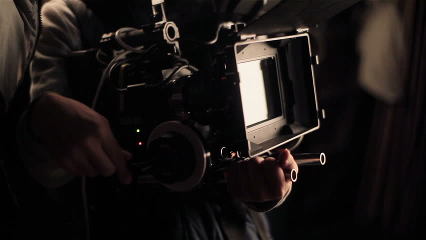 Cameraman adjusting camera before filming. Shooting with red camera. Close-up