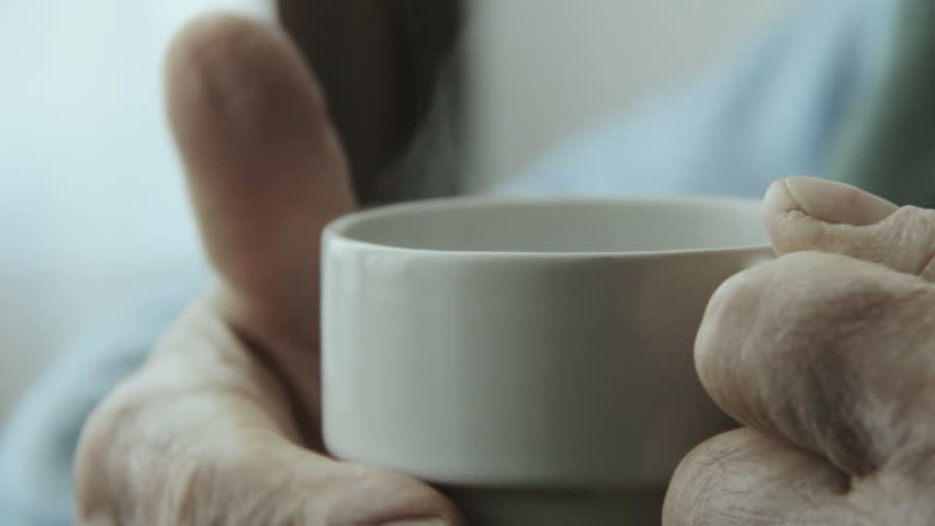 old man holding a cup of hot coffee with hands