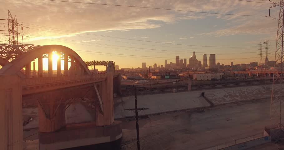 Sun peeking through iconic 6th Street Bridge arches at sunset as camera fly forward . Los Angeles, California. Aerial view, 4K UHD.