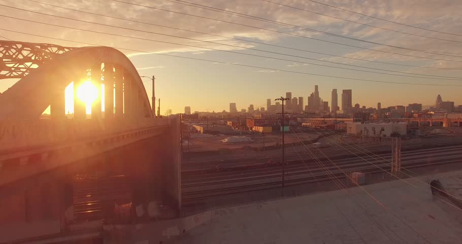 Sun peeking through iconic 6th Street Bridge arches at sunset as camera fly backward . Los Angeles, California. Aerial view, 4K UHD.