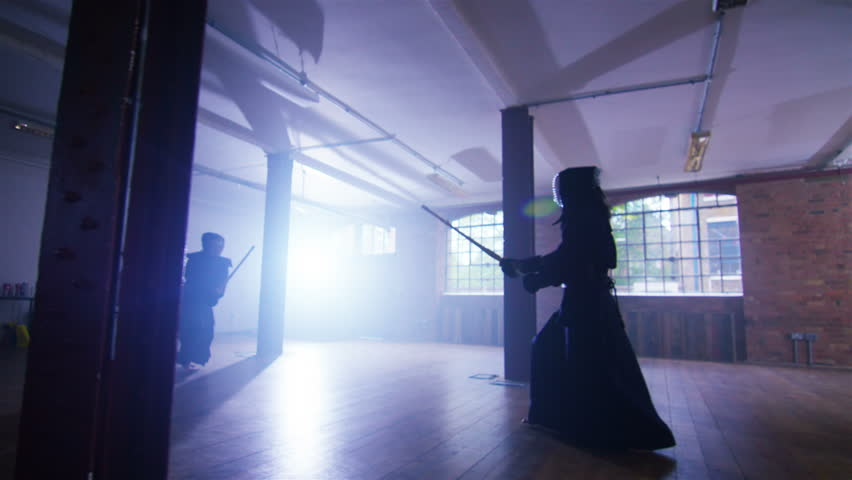 4K Japanese kendo fighters with bamboo swords competing in dark industrial building. Shot on RED Epic. #12421781