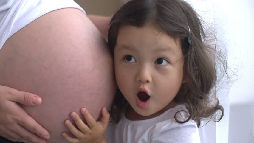 Curious little girl listening to her pregnant mother's belly,dolly shot, slow motion