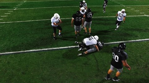 A football player gets tackled at the beginning of a play, view from above