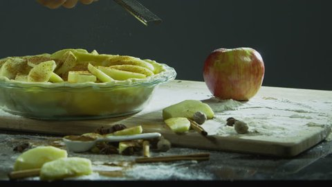 Grating cinnamon onto sliced apples to make apple pie