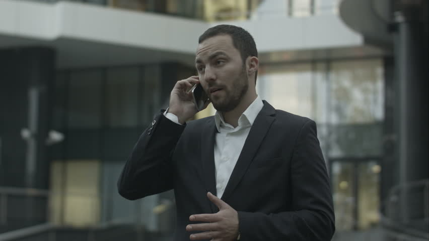 Displeased business man seriously talking by phone, standing outside the office | Shutterstock HD Video #12463781
