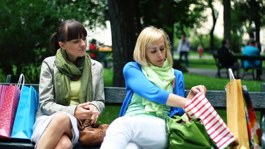 Two female friends checking shopping bags on park bench  | Shutterstock HD Video #1246783