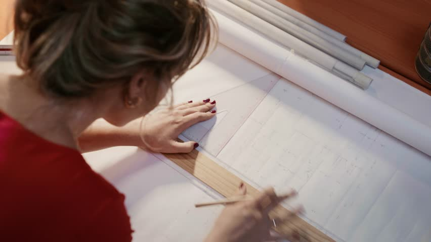 University student of Interior Design doing homework, completing housing project for final exam. The girl draws lines on a blueprint with a rule in her studio. Closeup, dolly shot