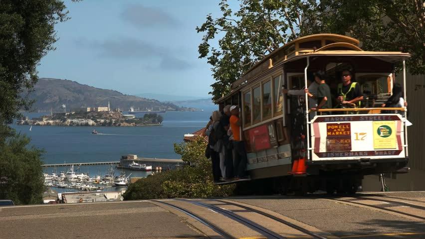 SAN FRANCISCO, CALIFORNIA, USA - AUGUST 30, 2015: a san francisco cable car drives downhill towards a distant alcatraz island