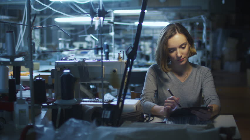Young woman garment worker is using tablet with a stylus at a clothing factory during a night shift. Shot on RED Cinema Camera in 4K (UHD) | Shutterstock HD Video #12505787