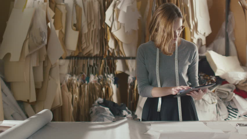 Clothing designer is working with a tablet in a workshop. Shot on RED Cinema Camera in 4K (UHD).