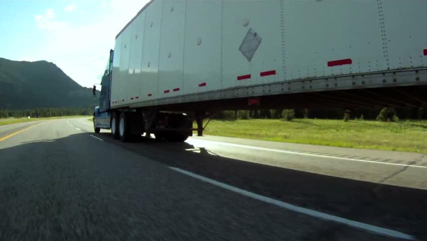 Vehicle pov shot of semi trailer truck traffic on highway