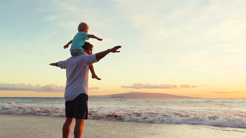 Father and Son Play Airplane Arms Raised Together at the Beach at Sunset. Happy Fun Smiling Lifestyle.