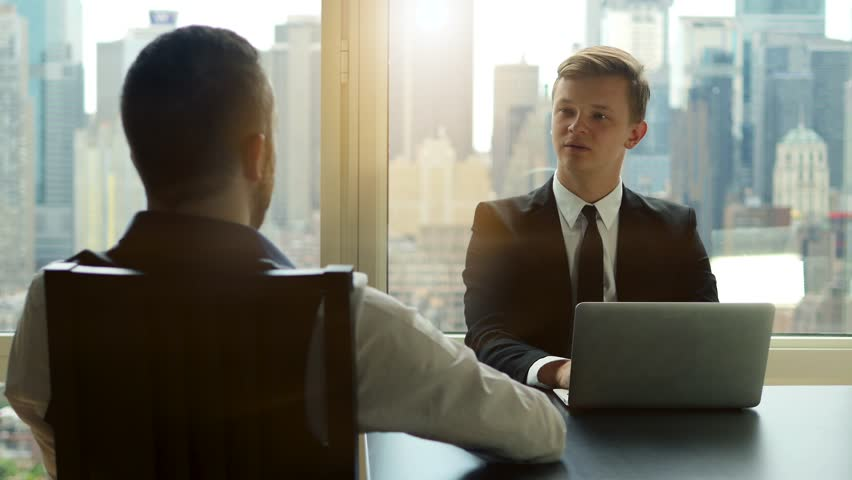 Two businessman having a meeting talking together in modern high rise office building. city skyline background. people job interview  | Shutterstock HD Video #12559892