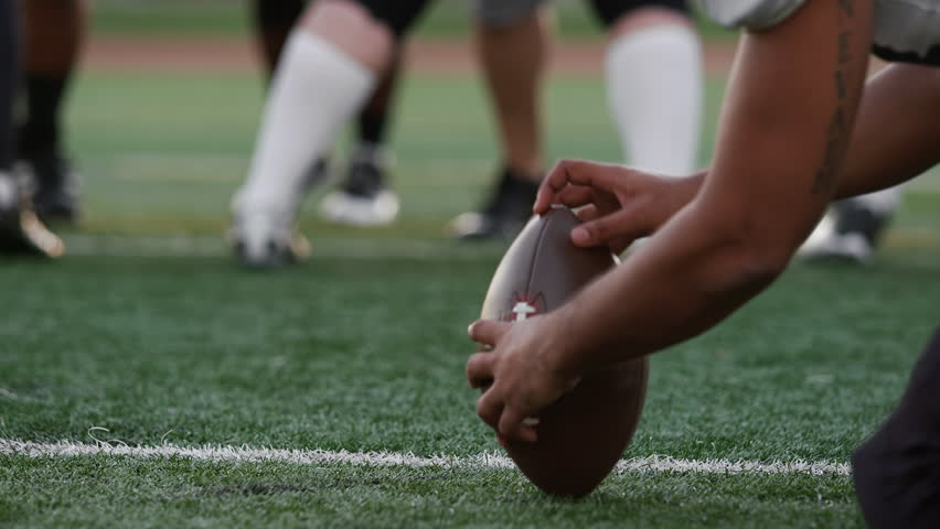 Close up of a football player kicking the ball toward the goal posts