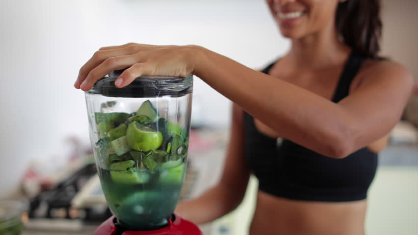 Young woman making a green juice on a blender | Shutterstock HD Video #12562994