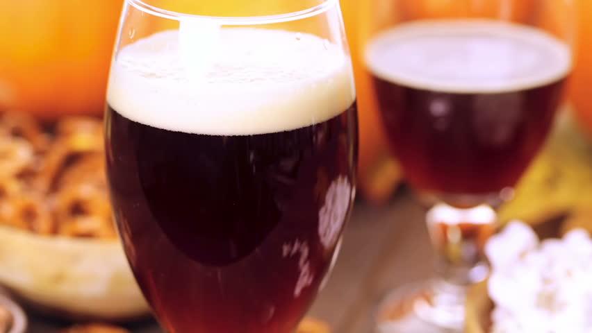 Craft pumpkin beer in beer glasses with salty pretzels and popcorn. | Shutterstock HD Video #12570737