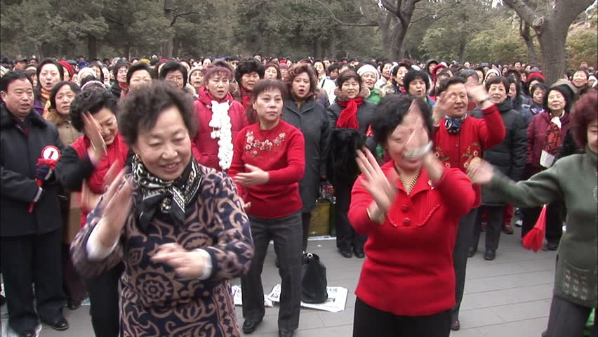 Beijing, China - February 2008: Women performing a traditional Chinese dance routine while a public choir sings a communist anthem in Jingshan Park, Beijing, China.