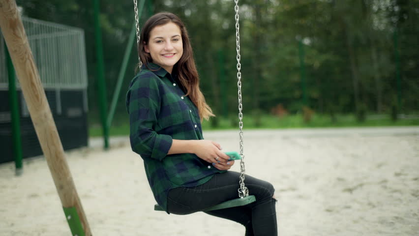 Happy girl swinging on the seesaw and using smartphone, steadycam shot  | Shutterstock HD Video #12574877