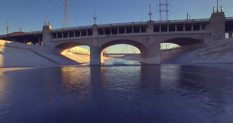 POV drive over water surface in LA river toward historic 7th Street Bridge over LA river in downtown of city of Los Angeles. 4K UHD.