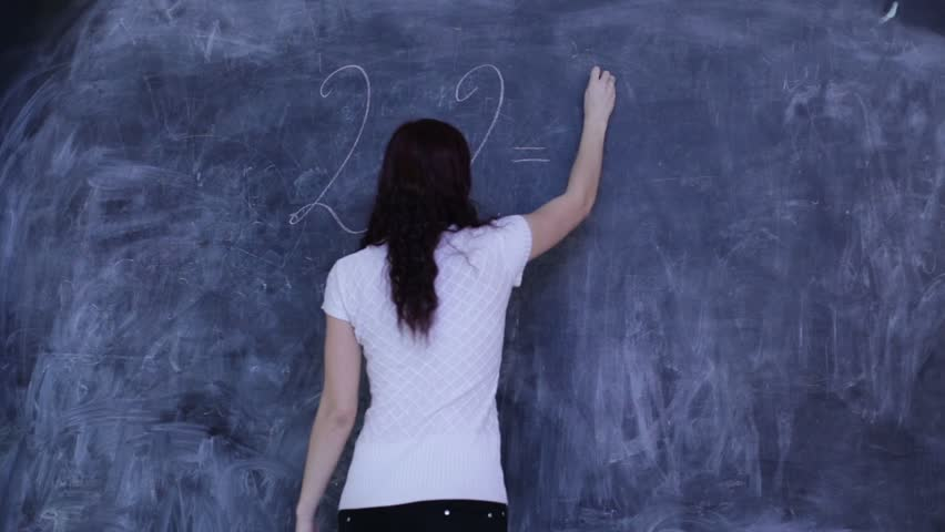 The woman wrote on the blackboard in the classroom mathematical equation