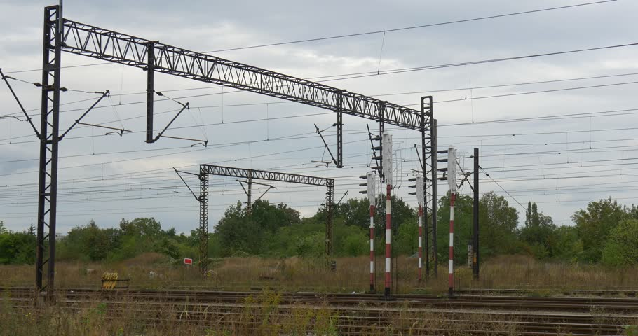 Supports of the railroad contact network, electric wires, lamp posts, input lights. Railroad tracks, rails. Green trees and bushes, dry grass. Grey sky, rain, cloudy autumn day, outdoors. Opole, | Shutterstock HD Video #12603746