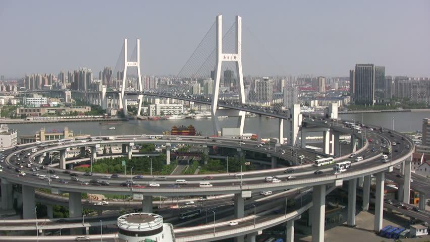 Nanpu bridge in Shanghai shows a massive roundabout, bridge, and heavy traffic. | Shutterstock HD Video #1261084