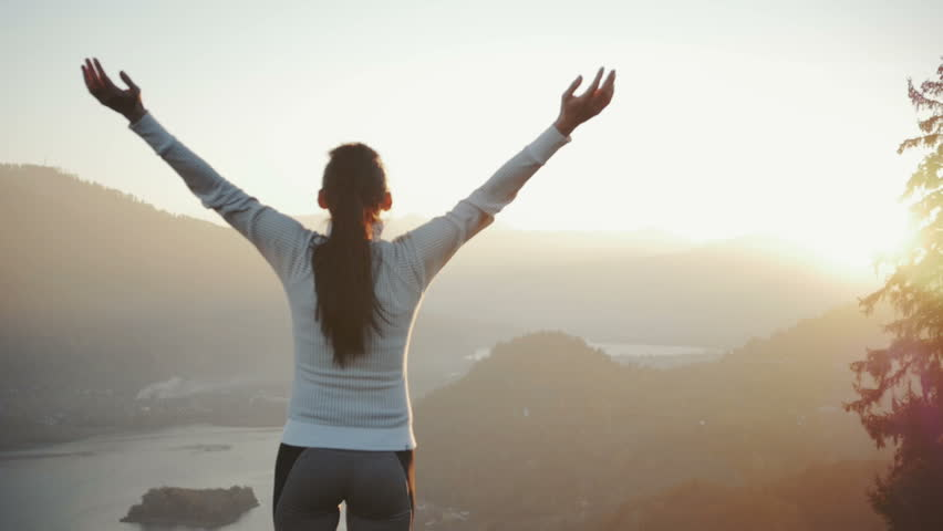 Woman fitness runner on top happy and celebrating success. Female runner on top of the world cheering in winning gesture.