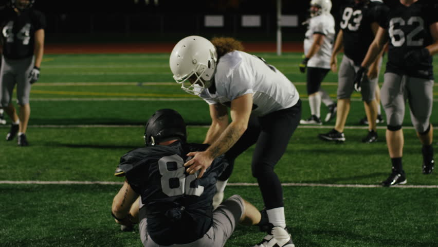A football player helps his opponent up off the ground after being tackled