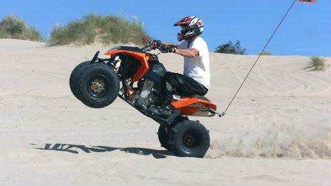 Cinemagraph - Man riding wheelie on quad atv in sand. Motion Photo.