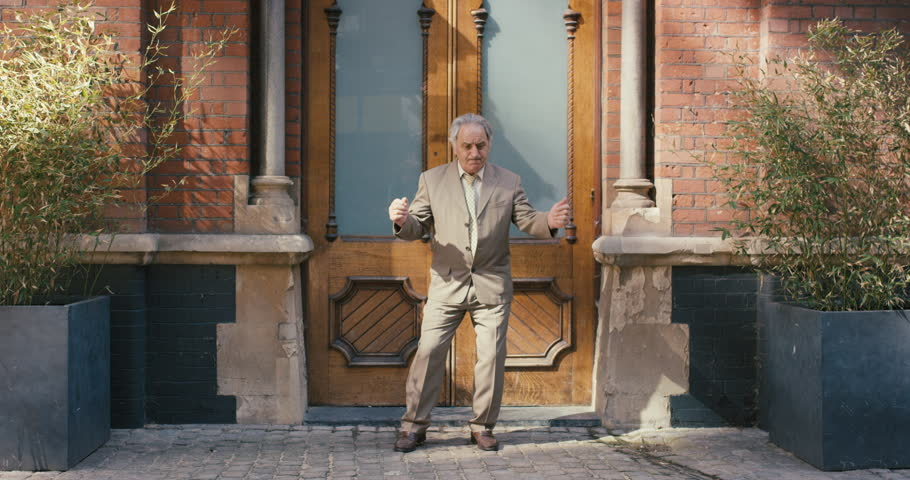 Happy elderly dancer man wearing suit in front of apartment funky street dancing freestyle in the city #12658718