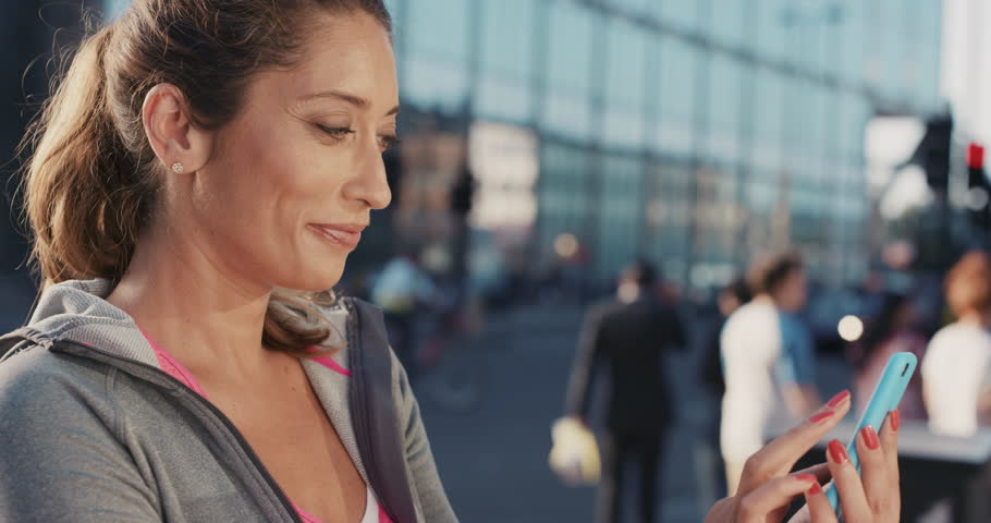 Slow Motion Portrait of happy beautiful fitness woman using smart phone sharing social media connection technology in city real people series | Shutterstock HD Video #12659330