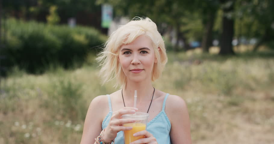 Slow Motion Portrait of happy beautiful caucasian woman drinking juice in the city real people series