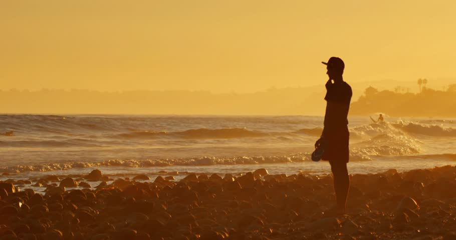 Cinemagraph - Silhouette of a young man standing on ocean beach looking on waves at sunset. 4K UHD Motion Photo.