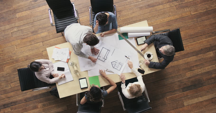 Top View of Business people meeting around boardroom table discussing architectural plans for new sustainable shared office space | Shutterstock HD Video #12702437