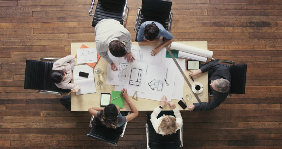 Top View of Business people meeting around boardroom table discussing architectural plans for new sustainable shared office space | Shutterstock HD Video #12702467