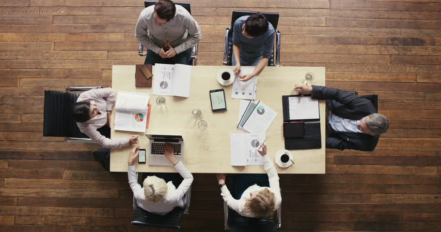 Top view diverse business people meeting at boardroom table discussing financial report using graphs and big data in trendy shared office space | Shutterstock HD Video #12707138