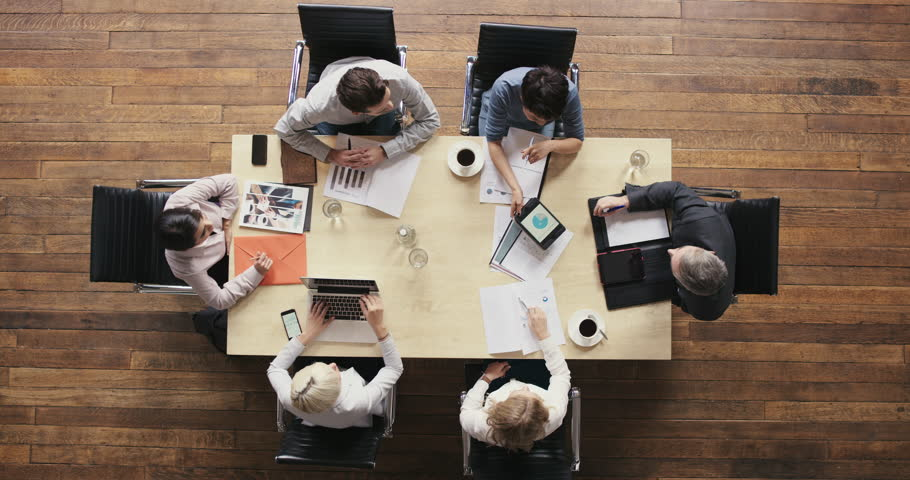 Top view diverse business people meeting at boardroom table discussing financial report using graphs and big data in trendy shared office space | Shutterstock HD Video #12707147