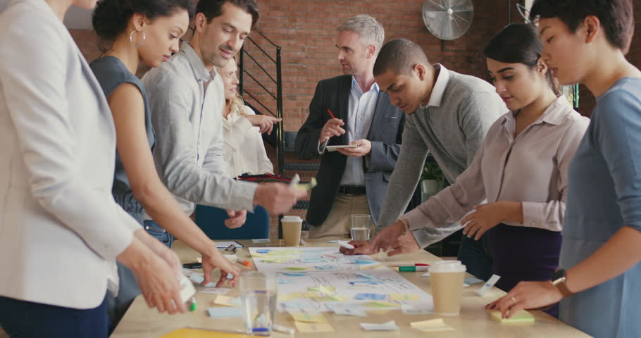 Multi-ethnic business team meeting brainstorming sharing new ideas Diverse team involved in teamwork in trendy brick office space steadicam shot across boardroom table shared work space | Shutterstock HD Video #12720515